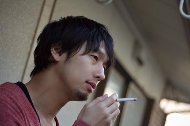 ベランダで煙草を吸う男性の写真