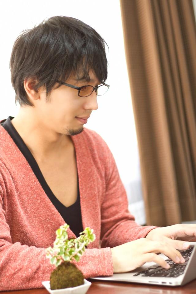 PCを触る色眼鏡をかけた男性の写真