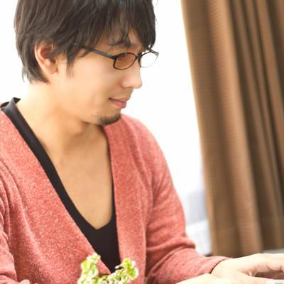 「PCを触る色眼鏡をかけた男性」の写真素材