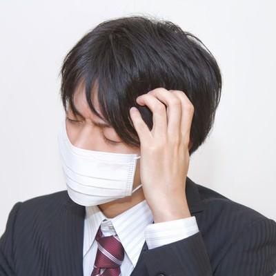 「マスクをして頭をかかえるスーツの男性」の写真素材