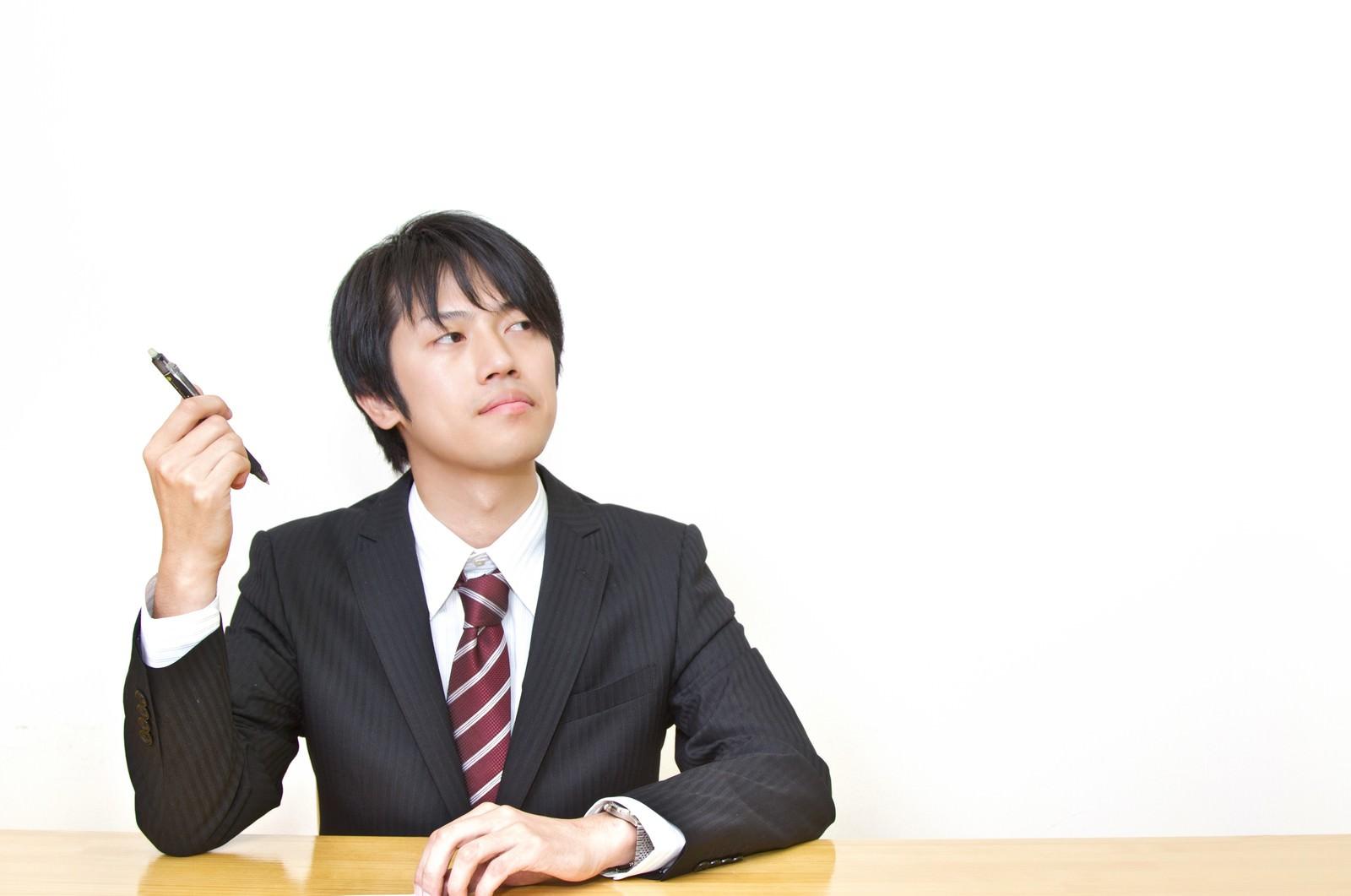 「ペンを持ち考えるスーツ姿の男性」の写真[モデル:Tsuyoshi.]