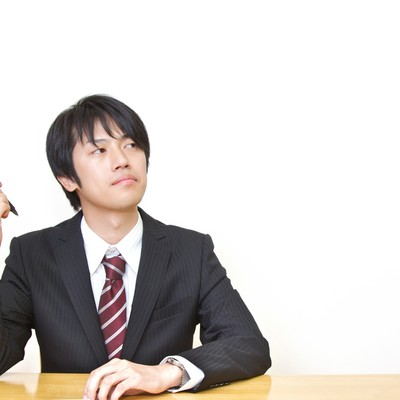 「ペンを持ち考えるスーツ姿の男性」の写真素材