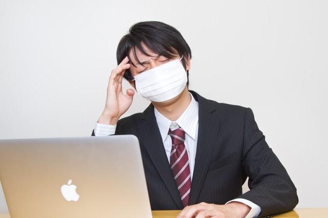 風邪をひいても残業するサラリーマンの写真