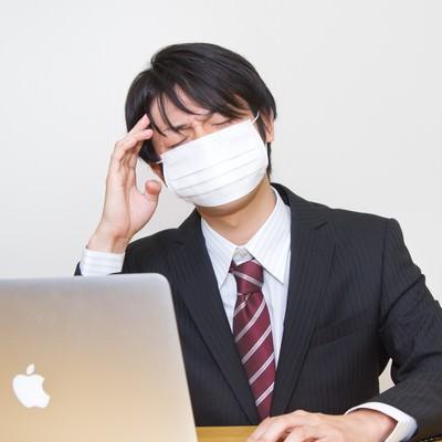 「風邪をひいても残業するサラリーマン」の写真素材
