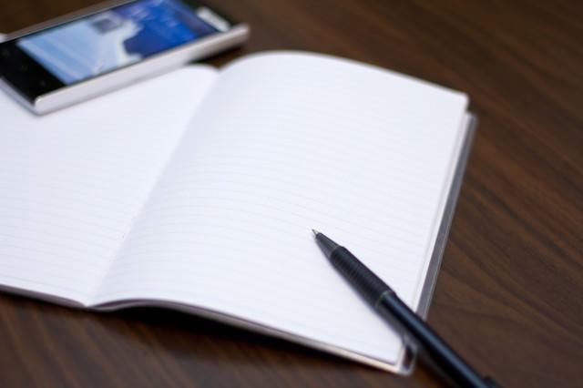 携帯とノートとペンの写真
