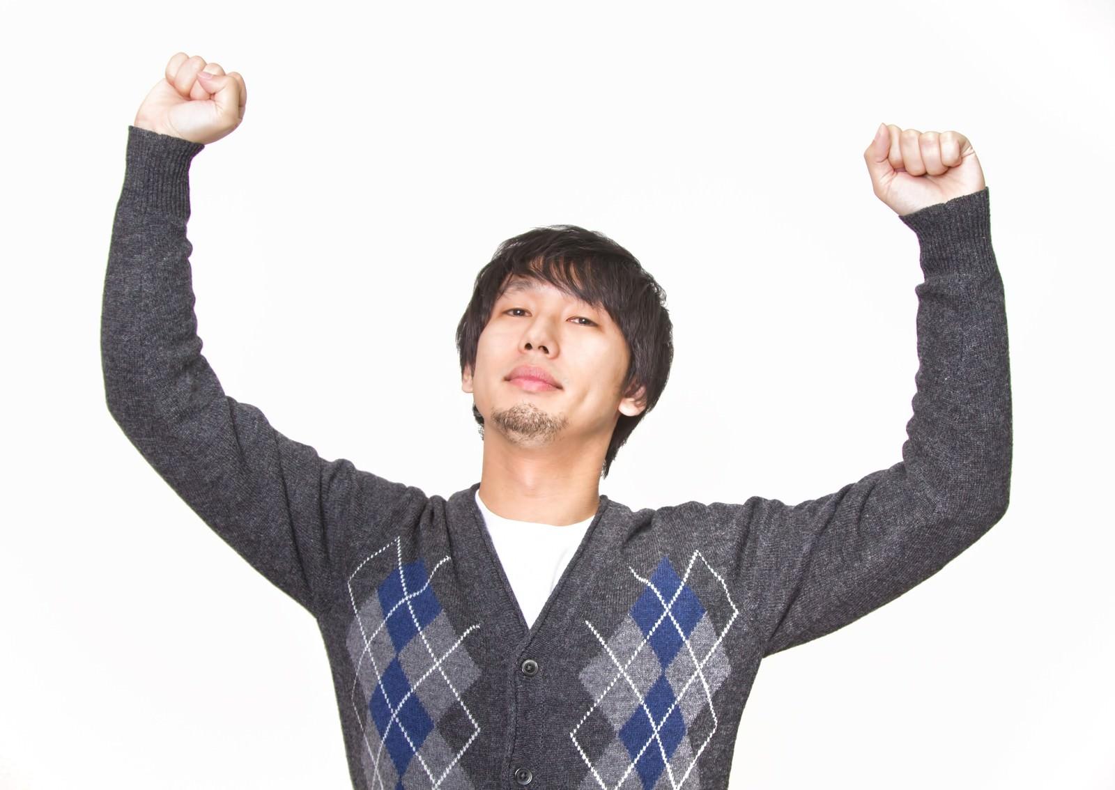 「『コロンビア!』っと腕を高々とあげる男性」の写真[モデル:大川竜弥]