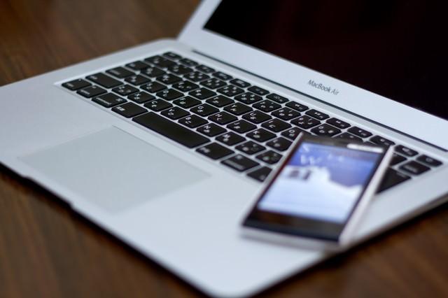 ノートパソコンの上に置かれた携帯電話の写真