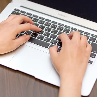 「MBAのキーボードを入力する手」の写真素材