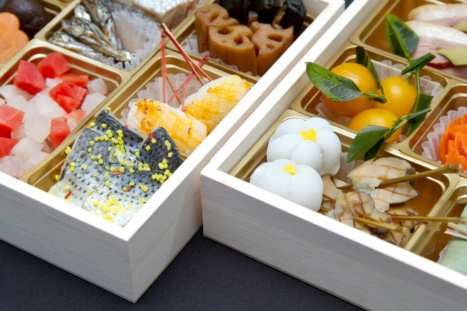 「桐の箱に入ったおせち料理」の写真
