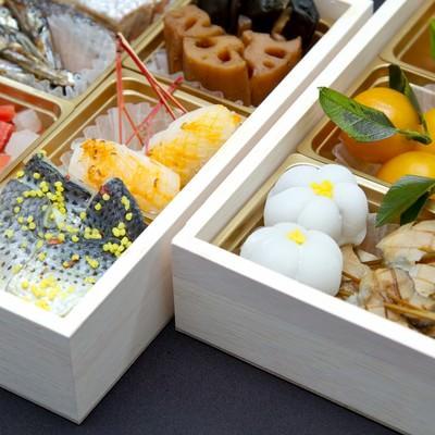 桐の箱に入ったおせち料理の写真