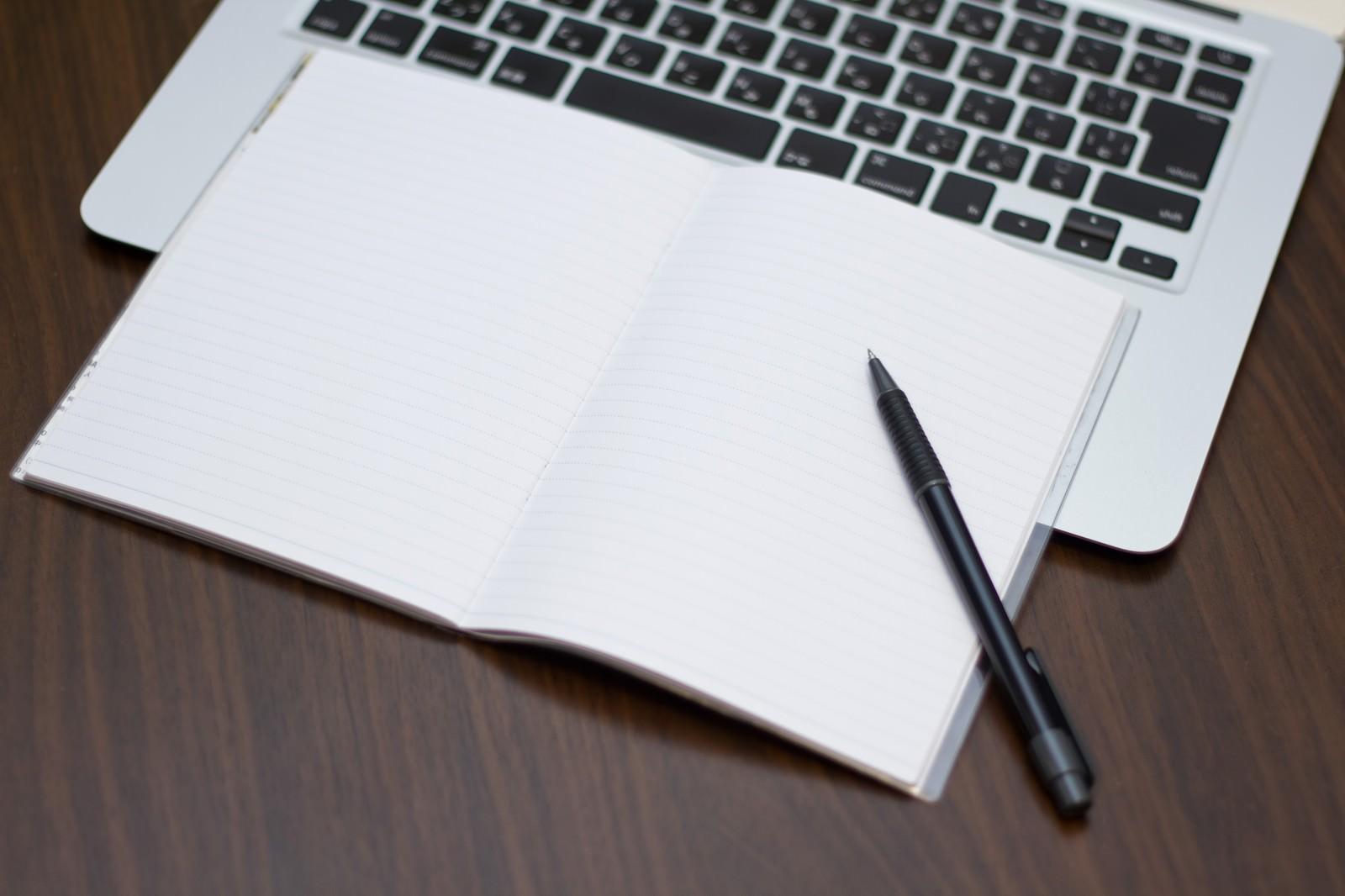 「ノートパソコンにメモとペン」の写真