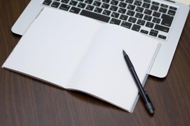 ノートパソコンにメモとペンの写真