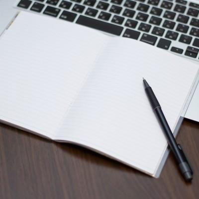 「ノートパソコンにメモとペン」の写真素材