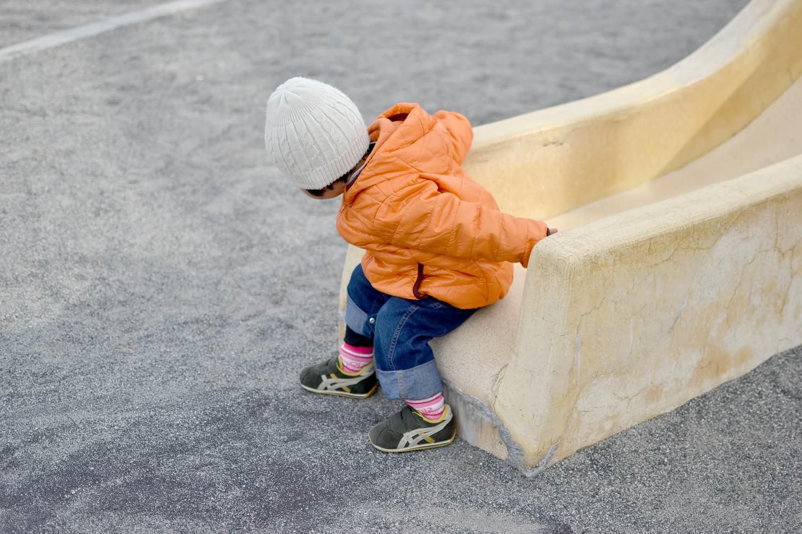 「滑り台から降りる子供」の写真