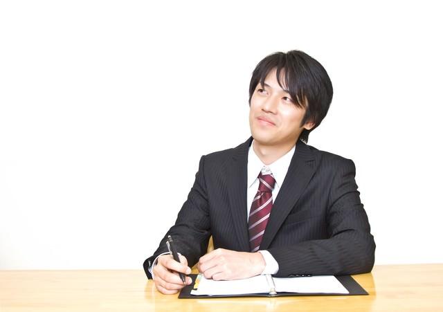 手帳を広げるスーツの男性の写真