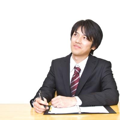 「手帳を広げるスーツの男性」の写真素材
