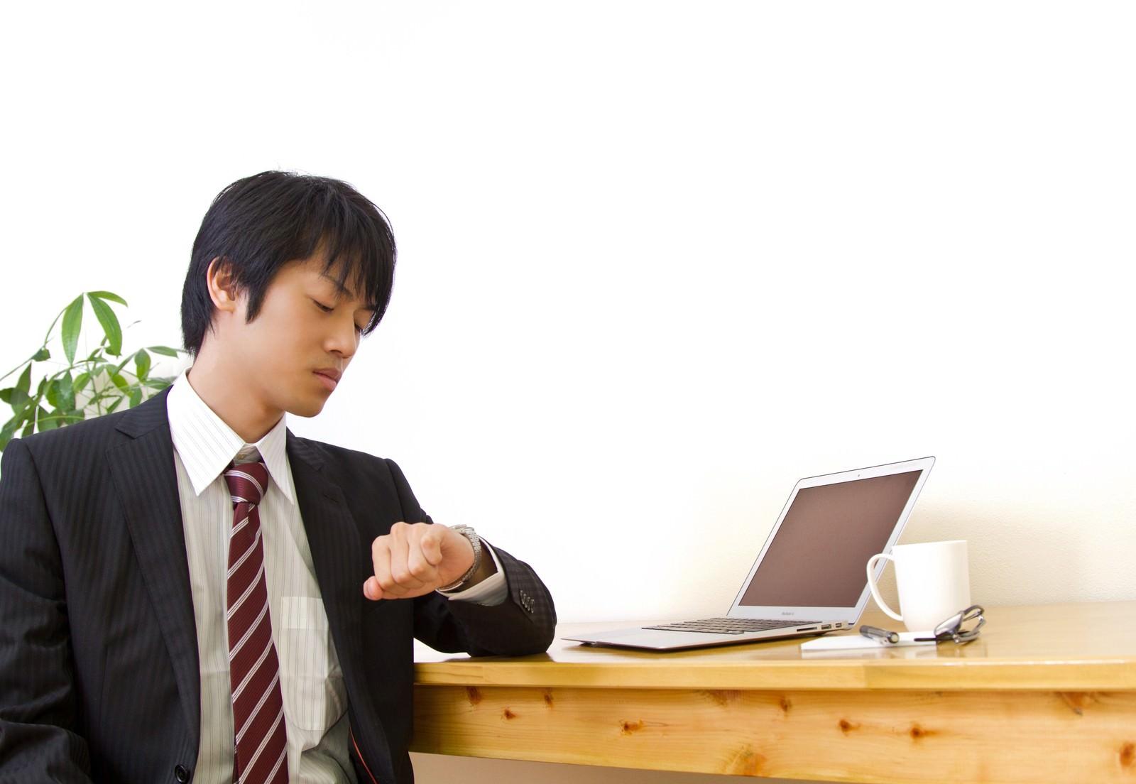 「時計を確認するスーツ姿の男性」の写真[モデル:Tsuyoshi.]