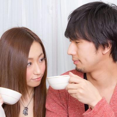 コーヒーカップを持って見つめ合う恋人の写真