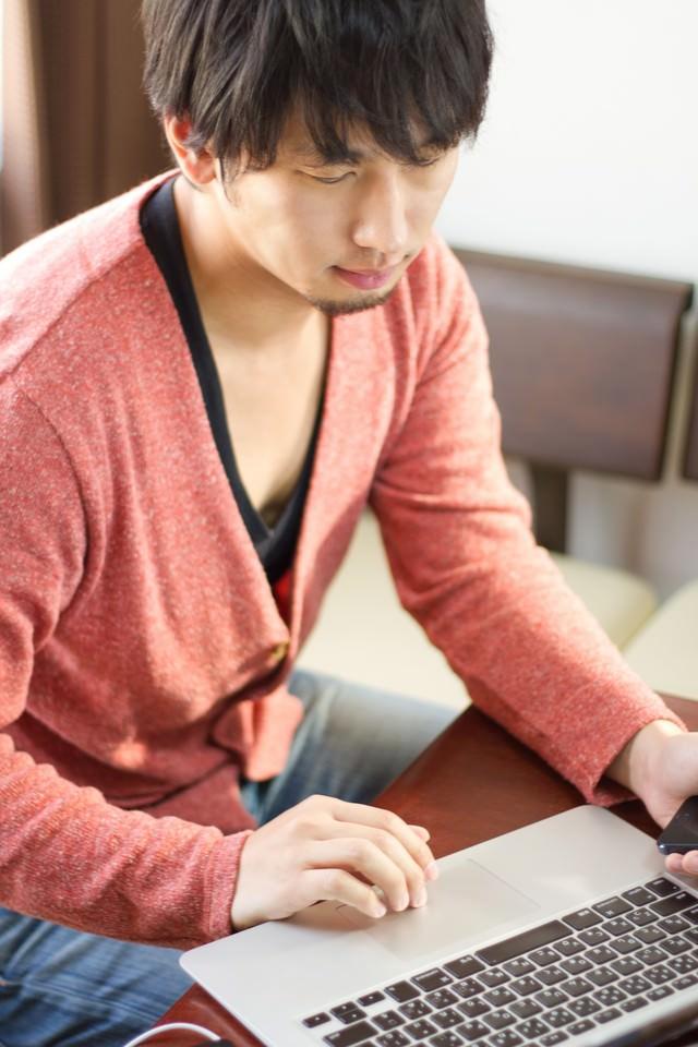 PCをチェックする男性の写真