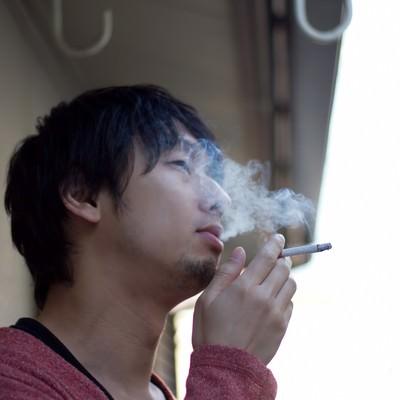 ベランダで煙草を吸う(煙モクモク)の写真