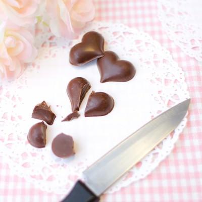 「ハート型のチョコレートを斬る」の写真素材