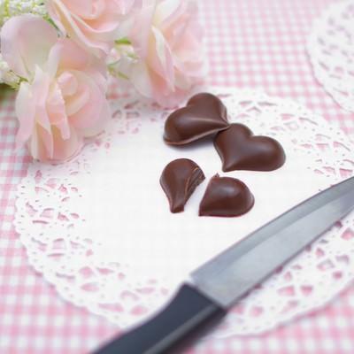 「ハートのチョコを真っ二つにナイフで切る」の写真素材