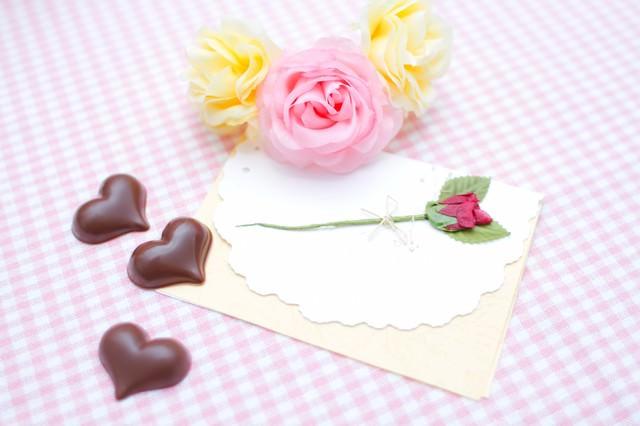 薔薇の造花と手紙・ハート型のチョコの写真