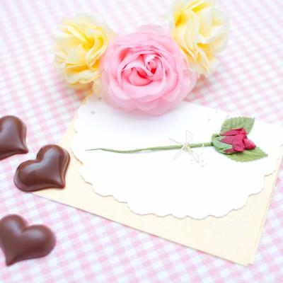 「薔薇の造花と手紙・ハート型のチョコ」の写真素材