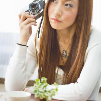 「レトロなカメラを持って肘をつく女性」の写真素材
