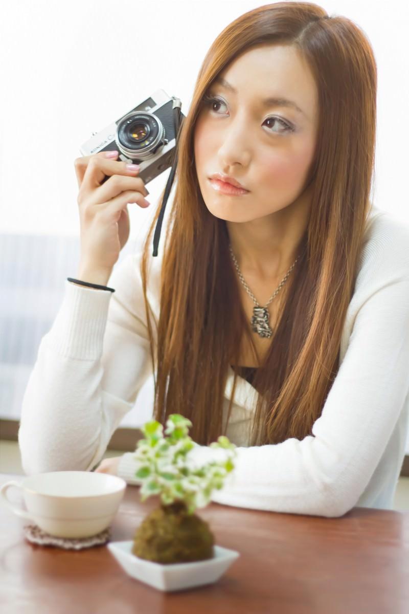 「レトロなカメラを持って肘をつく女性」の写真[モデル:北野佑々]
