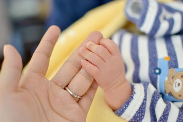 母の手を握る赤ちゃんの手の写真