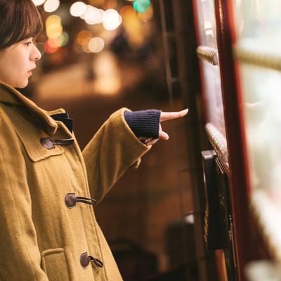 「自販機の「あったか~い」を買うコートを着た女性」の写真素材