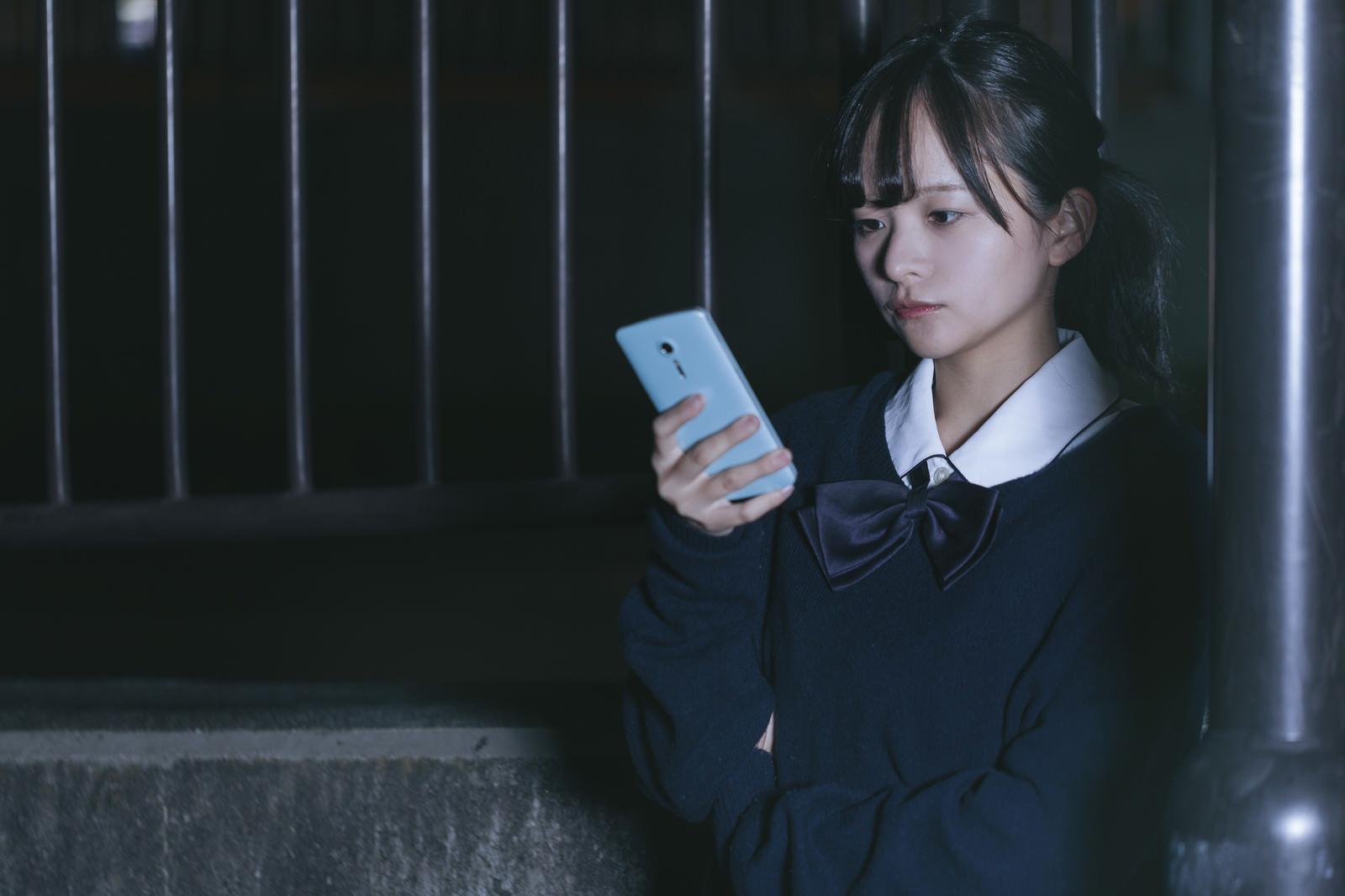 「スマホを使って追跡調査する女子高生探偵」の写真[モデル:千歳]