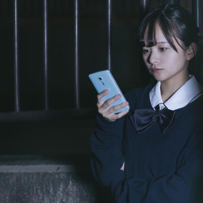 スマホを使って追跡調査する女子高生探偵の写真