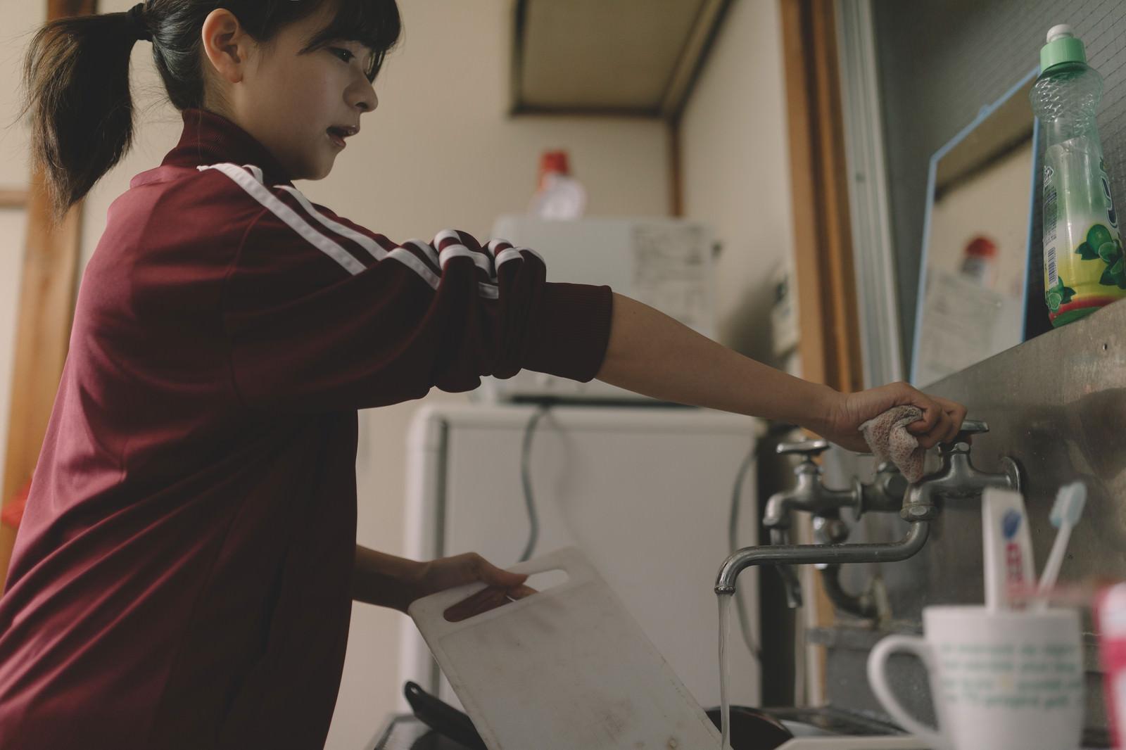 「溜まった洗い物をする貧乏学生(アパート暮らし)」の写真[モデル:千歳]