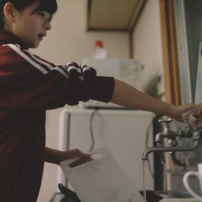 「溜まった洗い物をする貧乏学生(アパート暮らし)」の写真素材