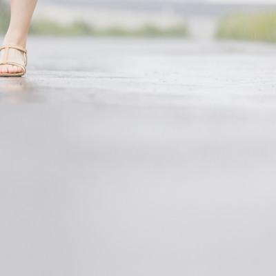 雨道を歩く(女性の足元)の写真