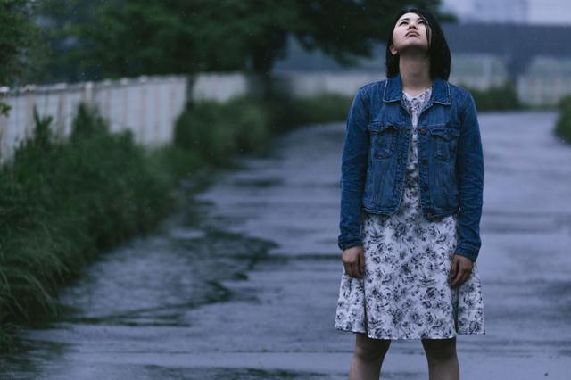 雨に打たれる女性の写真