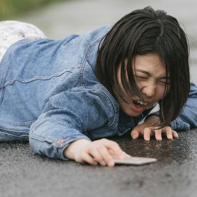 「歩きスマホで転倒し泣き叫ぶ女性(雨天)」の写真素材
