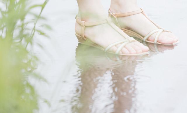 水たまりと女性の足元の写真
