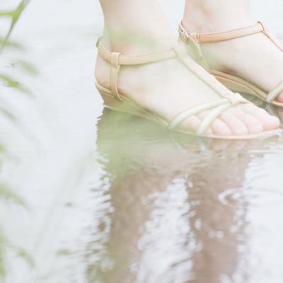 「水たまりと女性の足元」の写真素材