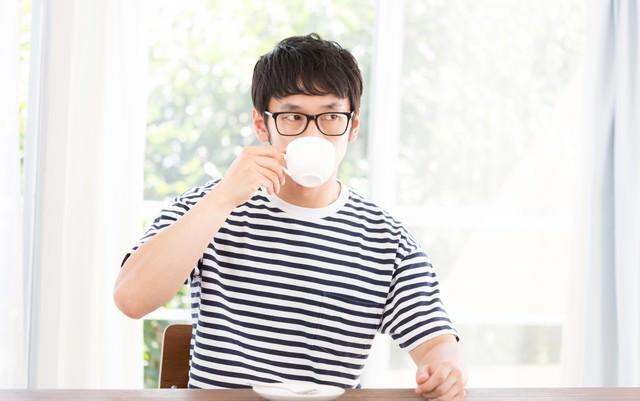 リビングで深煎りコーヒーを飲む男性の写真