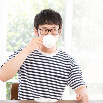 「リビングで深煎りコーヒーを飲む男性」の写真素材