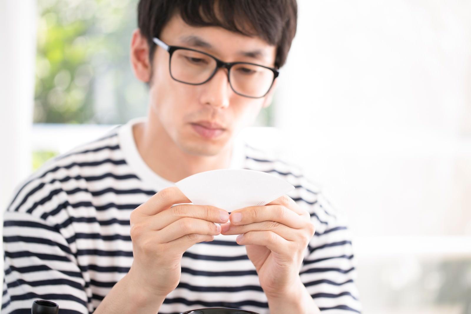 「ドリップコーヒーのペーパーフィルターをていねいに折るマメ男ドリップコーヒーのペーパーフィルターをていねいに折るマメ男」[モデル:大川竜弥]のフリー写真素材を拡大