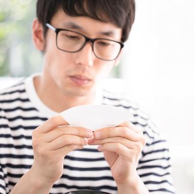 「ドリップコーヒーのペーパーフィルターをていねいに折るマメ男」の写真素材