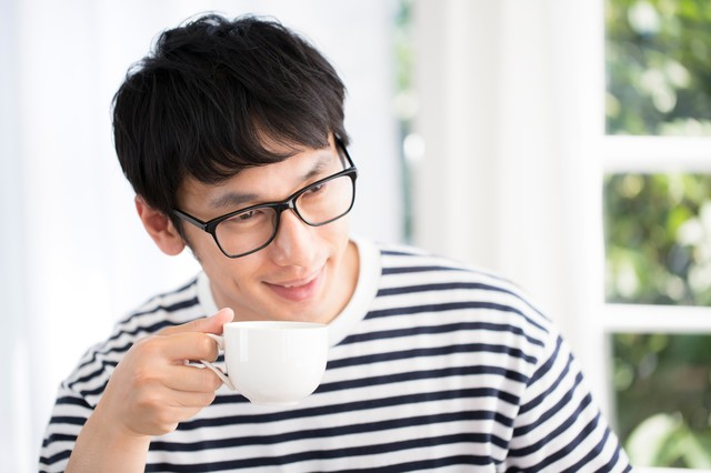 打ち合わせ中コーヒーを飲みながら相手の顔色を伺う人の写真