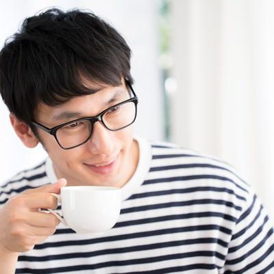 「打ち合わせ中コーヒーを飲みながら相手の顔色を伺う人」の写真素材