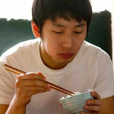 「ご飯をもぐもぐする男性」の写真素材
