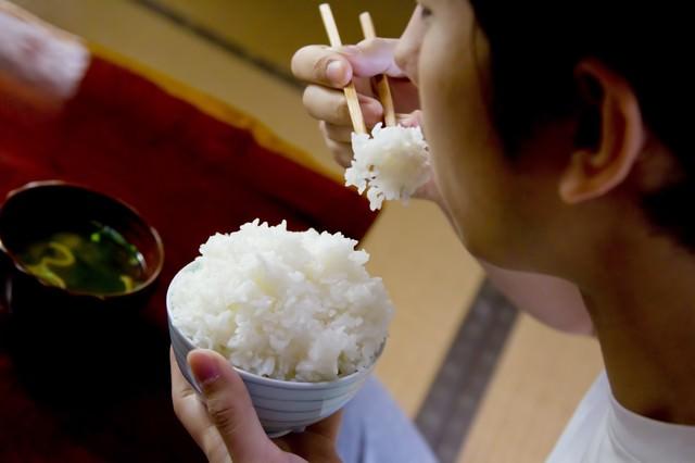 茶碗の白米を食べる様子の写真
