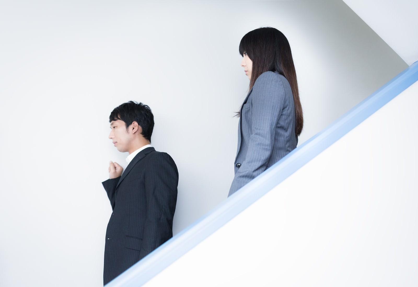 「オフィスの非常階段を下りながら非常に重要な件をする人事部長」の写真[モデル:大川竜弥 Lala]